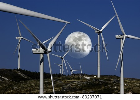 Windmills farm with full moon in background. - stock photo