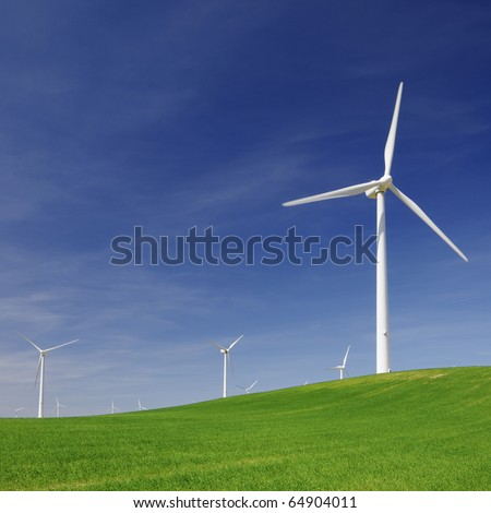 windmills for electric power production in an idyllic meadow