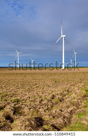Windmills for electric power production surrounded by agricultural fields in Polish country side. Poland, Europe.