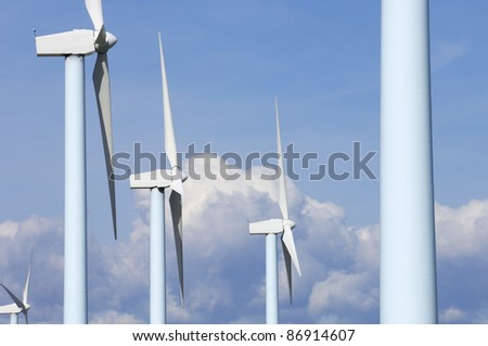 windmills for electric power production with cloudy sky - stock photo