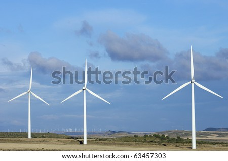 windmills for electricity production with blue sky and white clouds - stock photo