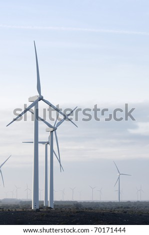 windmills for electricity production with cloudy sky - stock photo