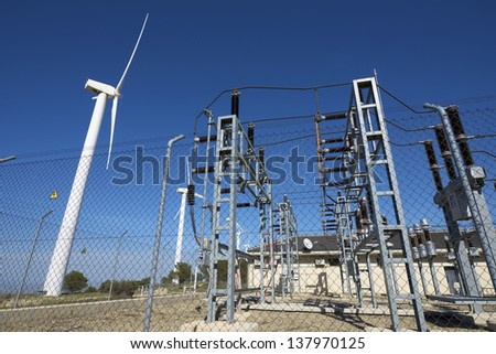 windmills for removable energy production and electrical substation - stock photo