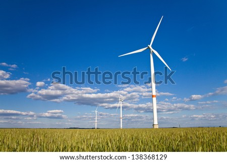 Windmills in a field of rye with blue sky with clouds - stock photo