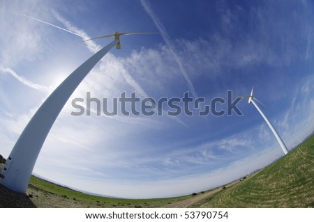 windmills in a field with blue sky - stock photo