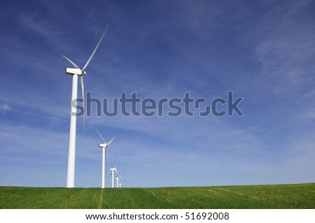 windmills in a green meadow with blue sky - stock photo