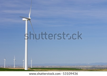 windmills in a meadow with cloudy sky - stock photo