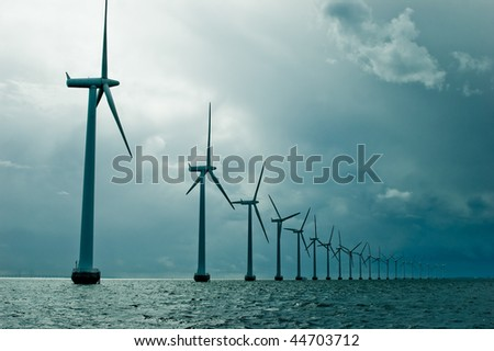 Windmills in a row on cloudy weather - stock photo