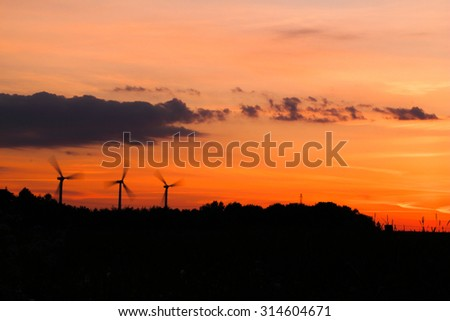 windmills in motion at sunrise sunset time. can be used for windmills, energy, nature, climate and environment themes - stock photo