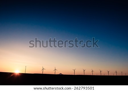 Windmills in sunset producing sustainable energy - stock photo