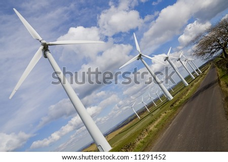 Windmills in windfarm shown at perspective view - stock photo