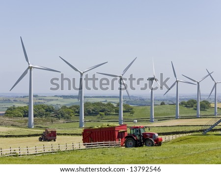 Windmills in windfarm with tractors working in foreground - stock photo