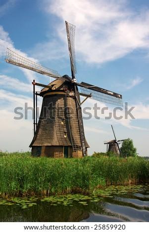 Windmills near the water in Kinderdijk in Holland - stock photo