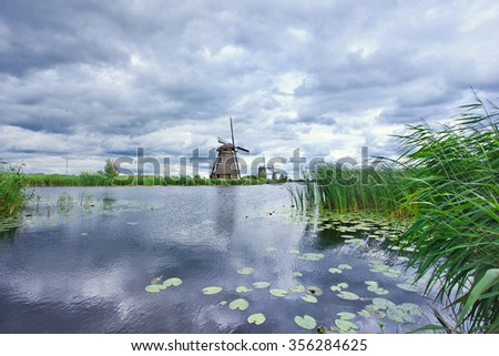 Windmills on a canal with dramatic shaped clouds, Kinderdijk, Netherlands - stock photo