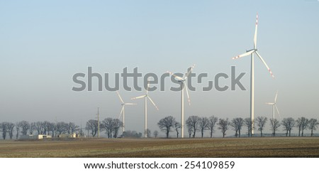Windmills on a frosted field - stock photo