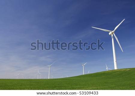windmills on a green hill with blue sky - stock photo
