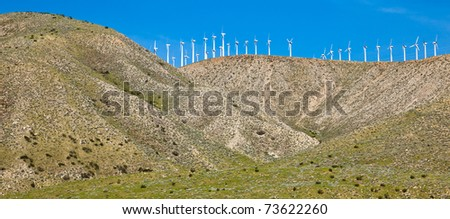 Windmills on a hill at the Palm Springs wind farm in California. - stock photo