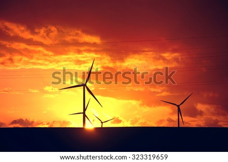 Windmills on the farm and sunset. Alternative ecological energy.