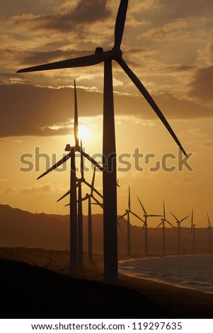 Windmills on the sea cost against sunset, north Philippines - stock photo
