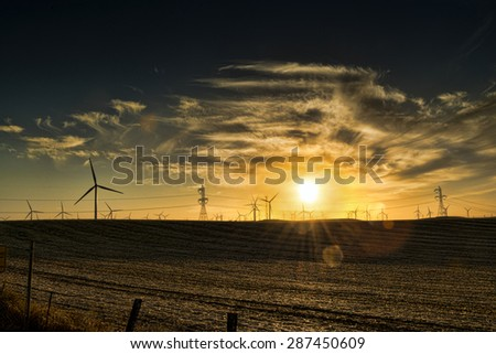 Windmills silhouetted by the setting sun - stock photo
