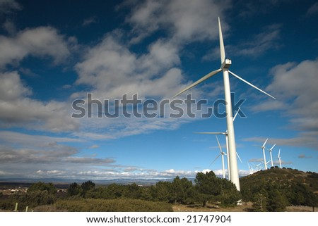 windmills under clouds sky