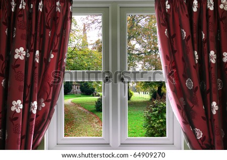Window and curtains with view of a English church garden - stock photo