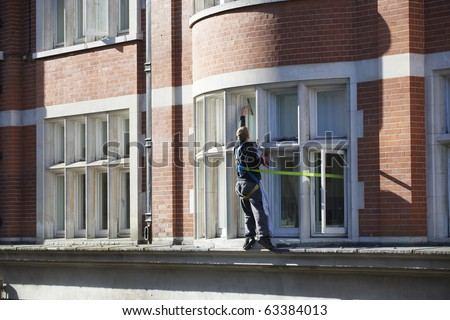 window cleaner standing on ledge with a safety harness