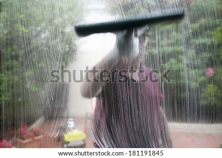 Window cleaner using a squeegee to wash a window.   - stock photo