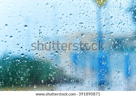 Window covered with rain drops on dull autumn day with view of city trees and building behind the window outdoors. Main focus on drops with blurred defocused background - stock photo