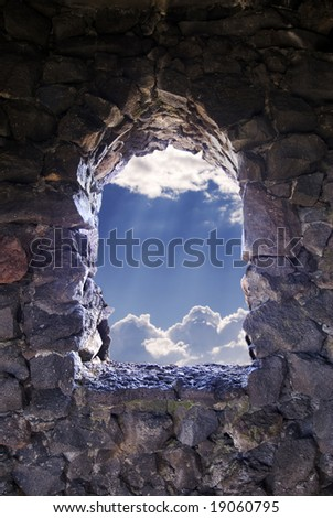 Window cut into a stony citadel with a view of puffy white clouds with the sun's rays burning through them. - stock photo