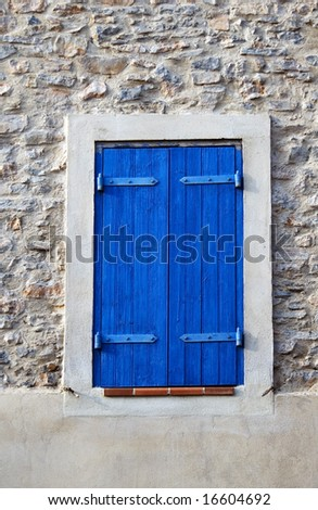 Window dark blue shutter in he stone wall, small town in France