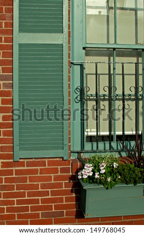 Window detail in old brick house with flowers - stock photo