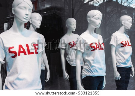 Window display with five mannequins wearing t-shirts with text Sale