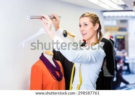 Window dresser or small business owner decorating shop display - stock photo