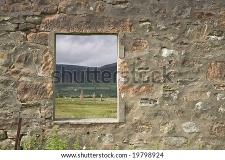 Window frame looking towards neolithic standing stones - stock photo