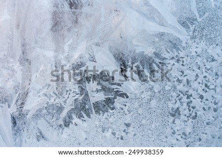 Window glass with hoarfrost drawings, taken from inside on the building in cold winter weather - abstract winter background - stock photo