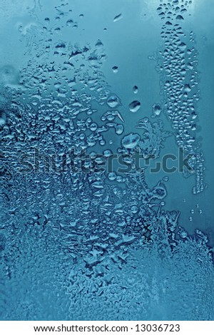 window glass with water drops and frost - stock photo