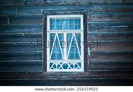 Window in a white frame on an old wooden wall. Toned. - stock photo