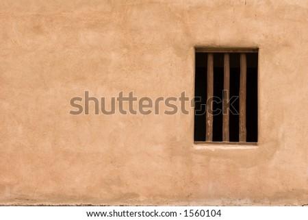 Window in adobe wall - stock photo