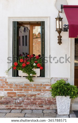 Window in an old house decorated with flower pots - stock photo