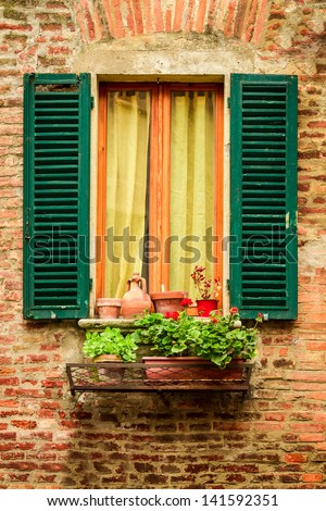 Window in an old house decorated with flower pots and flowers - stock photo
