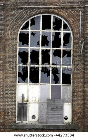 window in brick house with broken glass - stock photo