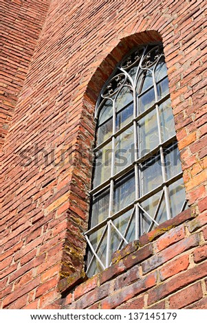 Window in brick wall of old church - stock photo
