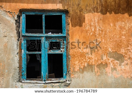 window in devastated house with yellow wall - stock photo
