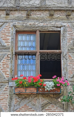 Window in traditional half timbered house decorated with a geranium filled window box, lead panel windows, and simple saltire and brick filled walls
