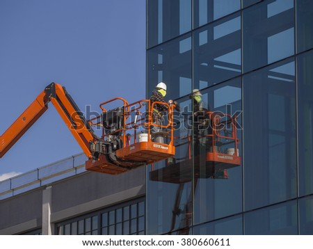 Window installer on a commercial building - stock photo