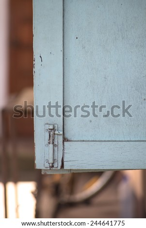 window latch on a old grungy timber window panel. - stock photo