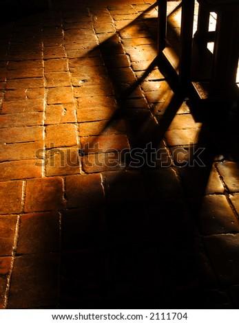 Window lit church pews on tile floor - stock photo
