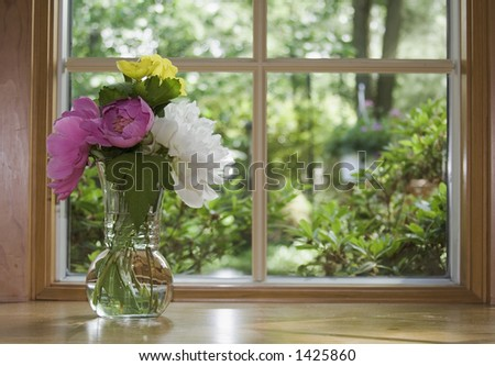 Window looking out to a beautiful Spring Summer view.  Floral Arrangement of peonies and other flowers. - stock photo