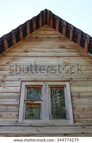 Window of a wooden rural lodge close up. - stock photo